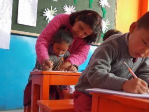 Teacher in Darjeeling, India teaching to write
