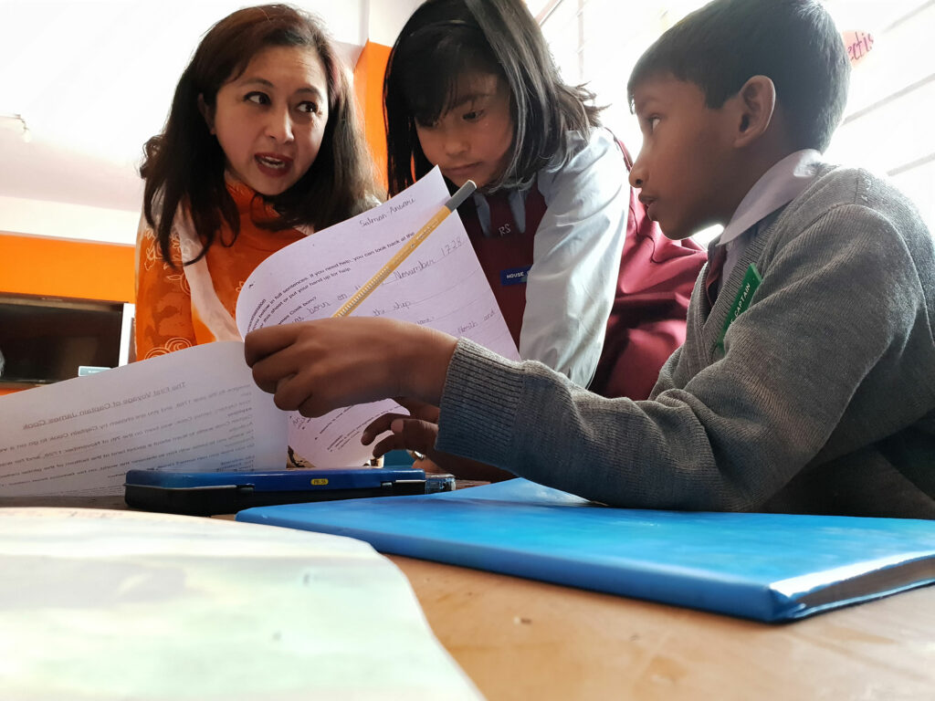 Teacher in India checking students' homework