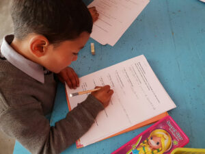 School Aid India student completing English homework