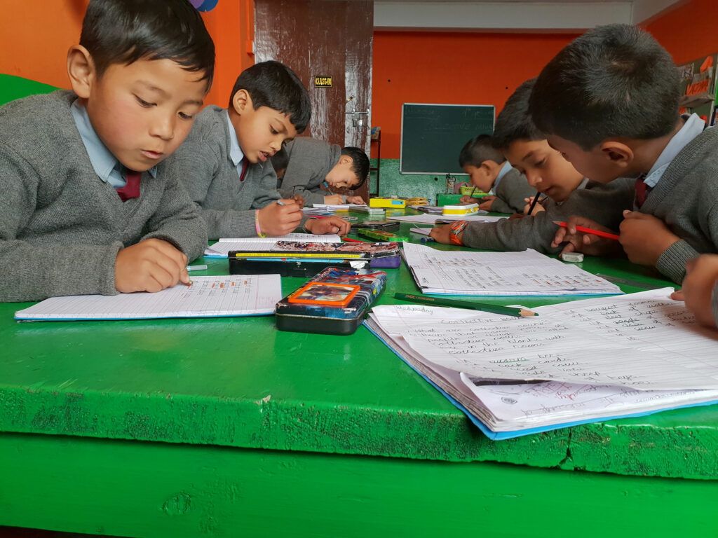 Students reading and writing in the Himalayas